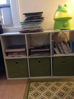 Books in the boy's bedroom. The books stacked on the top are library books.